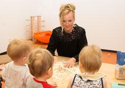 Gemeinsam kneten Monika Piekarski, Mitarbeiterin im Rahmen der Sozialen Teilhabe am Arbeitsmarkt, und Kinder der AWO Kita in Euskirchen den Teig. © Jobcenter EU – aktiv