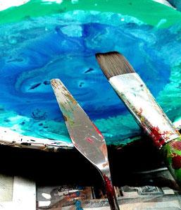 Spachtel, Pinsel und blaue Farbe auf einem Teller