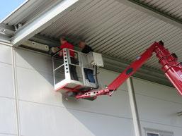 Mit einem Hubsteiger werden die Nisthilfen für Mauersegler unter dem Dach befestigt.