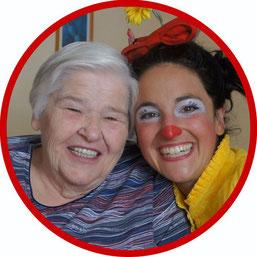 Bewohnerin in einem Seniorenheim sitzt im Rollstuhl und freut sich über den Besuch der therapeutischen Stuttgarter Clownin Angelina Haug