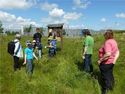 """Bei der Wanderung """"Rund um BMW"""" gab es vor einem """"Insektenhotel"""" am Werksgelände Erklärungen zu Flora und Fauna und zu Artenschutzprojekten des NABU. Foto: Bernd Hoffmann"""