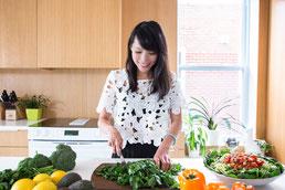 Portrait corporatif coach professionnelle nutritionniste femme asiatique Julie Doan dans sa cuisine en train de couper du persil à Montréal dans le quartier Villeray par Marie Deschene photographe Pakolla
