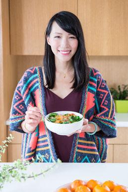 Portrait photo coach professionnelle nutritionniste femme asiatique Julie Doan montrant le repas qu'elle a cuisiné à Montréal dans le quartier Villeray par Marie Deschene photographe Pakolla