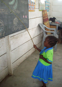 Ein Mädchen lernt englische Begriffe an einer Tafel.