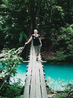 Blonde Frau auf Brücke über einem Fluss in Costa Rica.