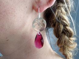 photo de profil dune jeune femme portant une boucle d'oreilles en argent massif et gouttes en cristal rouge rubis