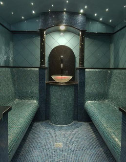 Spa-like steam room shower with Wedi pan with center drain, flanked on both sides by curved benches covered in blue-green glass mosaics, with a center black granit countertop with a honey onyx vessel sink. The walls and ceiling are covered in glass tiles.