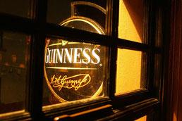 Pub mit Guinness-Schild am Abend durch ein Fenster nach außen zu sehen