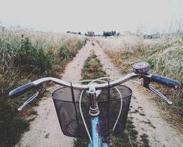 Feldweg über einen Fahrradlenker gesehen.