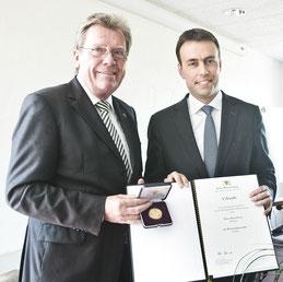 Heinz Peters erhält aus den Händen von Finanz- und Wirtschaftsminister Nils Schmid die Wirtschaftsmedaille des Landes