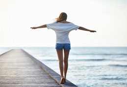 Femme en équilibre sur un ponton montrant le chemin pour retrouver un équilibre harmonieux par l'intégration des réflexes archaïques