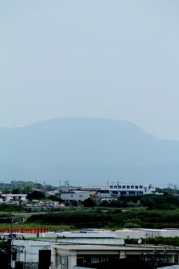 大陸からの黄砂の飛来で街並みがどんよりとした石垣島。於茂登岳はかすんで見えた=7日午後0時すぎ、県八重山事務所5階から撮影
