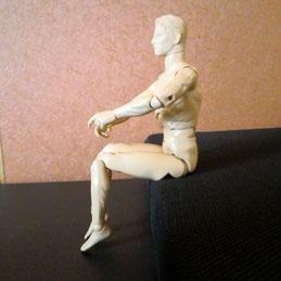 イスに座って かかとを上げる人形
