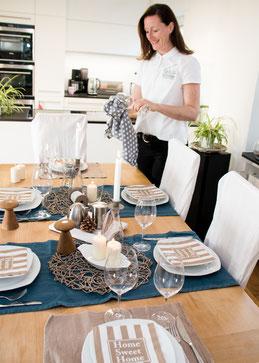 Dame in einer Küche mit Esstisch beim Polieren von Gläsern