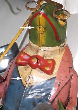 Zwei Laschen werden durch eine winzige Scheibe mit Schlitz gesteckt und umgebogen. Eine Methode, die insbesondere ab etwa 1900 bei figürlichem Blech die Körperhälften zusammenhielt.