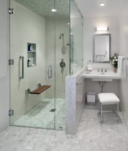 All-white bathroom with a white floating sink on the right side with white stool. On the left is a curbless shower with grab bar and shower bench.
