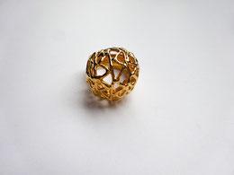 Une bague boule dorée très ajourée est vue de dessus.