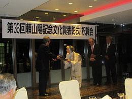 財団の橋本宗利会長から表彰状を受け取る