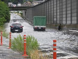 ゲリラ豪雨で瞬く間に雨水が溜まり、立ち往生するトラック(右) 田方陸橋下。陸橋の上では心配そうに見下ろす人の姿も見える。