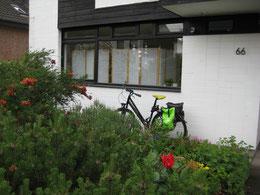 Gut sichtbares, großes und einladenes Fenster der Praxis zur Straße in der Eintrachtstr. 66 in 45 478 Mülheim an der Ruhr. Im Vorgarten sind rote Rosen und blühende Sträucher zu sehen. Das Fahrrad gehört der Therapeutin.