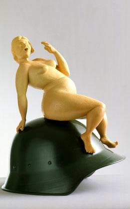orangefarbene Figur mit erschrecktem Ausdruck, die auf einem grünen Schutzhelm sitzt