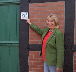 Angelika Lüters zeigt stolz auf die an der Scheune angebrachte Plakette, die ihr Schwalbenfreundlichkeit bescheinigt.