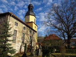 Dreifaltigkeitskirche in Jena-Burgau mit dem ehemaligen Pfarrhaus im Hintergrund.