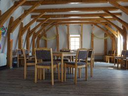 Im wohnlichen Gemeinderaum dominiert das Balkenwerk der ursprünglich gewölbten Kirchendecke