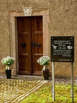 Eingangsportal mit dem Baujahr der Kirche, Erinnerungstafel an den Vogelpastor Christian Ludwig Brehm