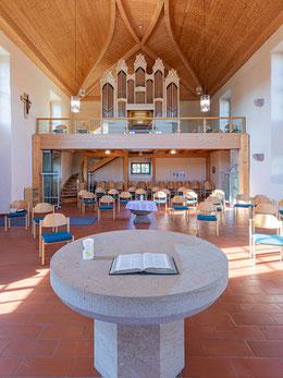 Heller, geräumiger Kirchenraum in alten Mauern mit Altar und Taufstein