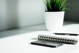 Arbeitsplatz von Alexandra Jordan mit Notizbuch, Stift und Smartphone.
