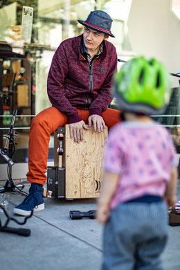 Kind sieht beim Cajon spielen zu