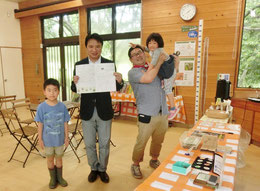 ●西岡市長とスタッフの山田ファミリーです。市長はスタンプラリーの台紙を掲げられています。