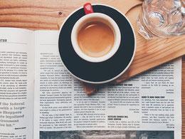 Kaffeetasse und Wasserglas auf Holzbrett stehen auf Zeitschrift.