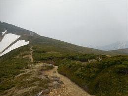 ▲銀玉水前の残雪を登り切れば小屋は目前!雪もなく快適な歩行。しばらく進むと中央左奥に大朝日岳山頂避難小屋がみえます。