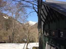 葉っぱの出ていない今だけ可能な建物入口と大朝日岳のツーショット