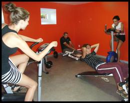 Salle de sports avec banc de musculation, rameur, vélos, planche à abdos et steppeur