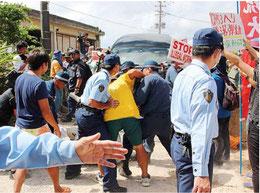 倒れこみ車両通行を妨害する抗議者に続こうとする別の抗議者と制止しようとする警察官ら=12日、高江の不時着現場に続く農道前