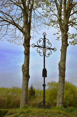 Drucat- La croix en fer forgé avec ses quatre coeurs dans les quadrants et sa plaque de cuivre presque intacte qui nous raconte l'histoire de cette croix