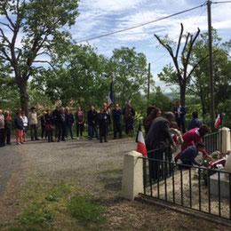 Les jeunes déposent la gerbe de fleurs au pied du monument aux morts.