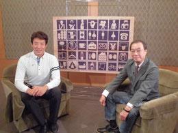 ※左が松岡修造さん、右が原田維夫先生。1964東京オリンピックで開発された「ピクトグラム」を背景に番組収録後の記念撮影。