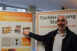 Tischlermeister Matthias Sieg präsentiert Fotos einiger Gesellenstücke. Bei der nächsten Ausbildungsmesse würde er aber gern die echten Stücke zur Anschauung mitbringen. Foto: Frank