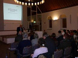 Michael Brockerhoff begrüßt die beiden Referenten und das Publikum im Stiftssaal von St. Margareta.
