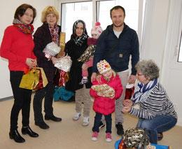 Britta Schumacher (1. v.l.),  Elke Bonn (2. v.l.) und Mechthild Schmölders (r.) übergeben Geschenke in der Flüchtlingsunterkunft Karlsbader Straße.