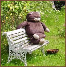 großer Bär auf Gartenbank im Garten von AMARELLA Räucherwerk