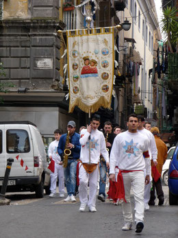 Vor Ostern ziehen Musikgruppen durch die Altstadt. Die schweren Standarten mit den Heiligen werden mit Gürteltaschen gehalten.