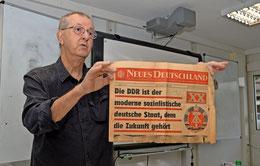"""Peter Rompf präsentiert den Schülern eine klassische DDR-Devotionalie: Ein Exemplar des SED-Zentralorgans """"Neues Deutschland"""" vom 7. Oktober 1969."""