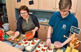 Schüler Malte Huch zeigt der Bolzumer Ortsbürgermeisterin, wie man die Pizzabrötchen zubereitet.  (Kühn/HAZ)