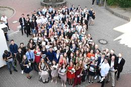 Mit Zeugnis und Blümchen: Die Haupt- und Realschüler der KGS posieren für ein Gruppenfoto. Foto: Benedikt Thebes