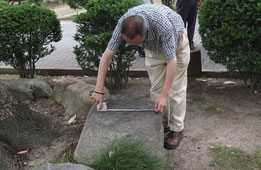 クスノキの下の「刻印石」を計測する大澤さん